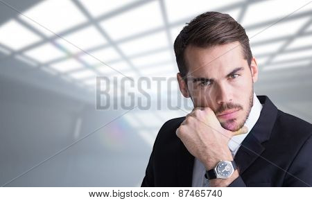 Cheerful businessman posing with hand on chin against white room with windows at ceiling