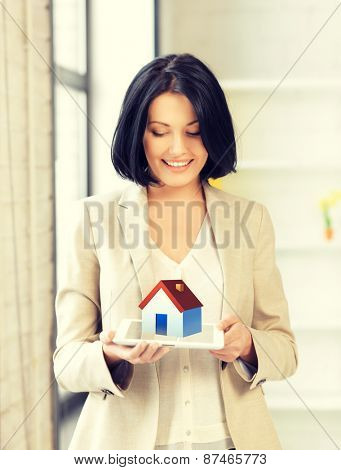 picture of woman holding tablet pc with house illustration