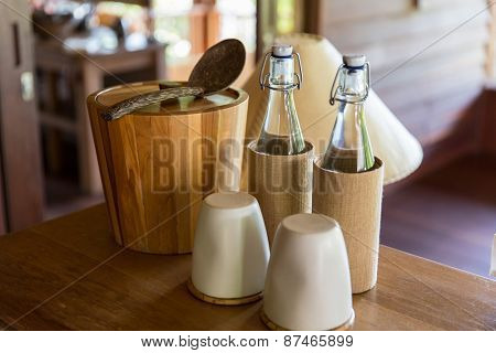 tableware and kitchenware concept - couple of bottles and glasses on table at hotel room