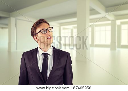 Young businessman thinking and looking up against white room with windows