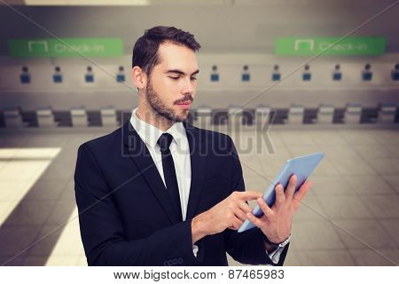 Cheerful businessman touching digital tablet against airport