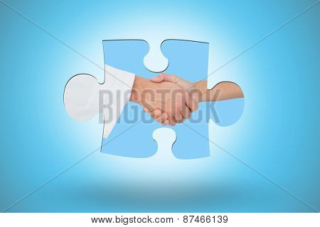 Extreme closeup of a doctor and patient shaking hands against blue background with vignette