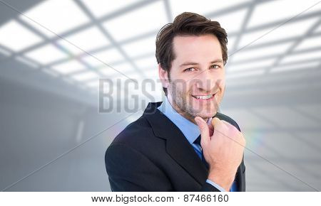 Businessman touching his chin while smiling at camera against white room with windows at ceiling