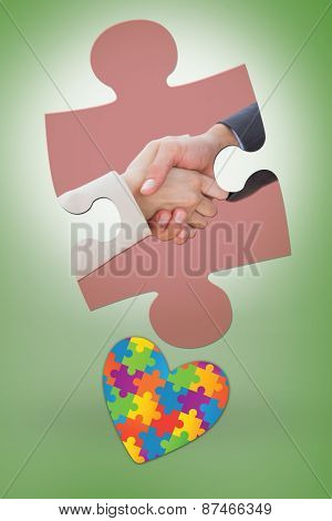 Close up on partners shaking hands against green vignette