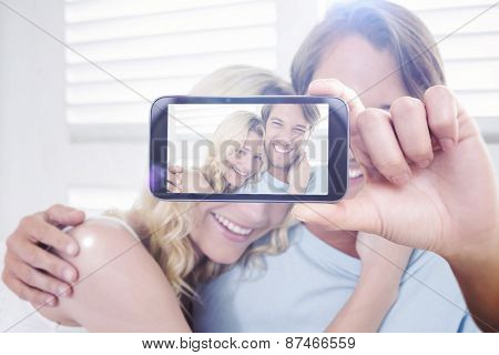 Hand holding smartphone showing against cute casual couple sitting on couch laughing at camera