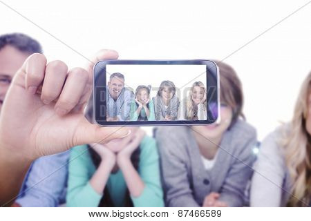 Hand holding smartphone showing against cute family lying on the floor smiling at camera