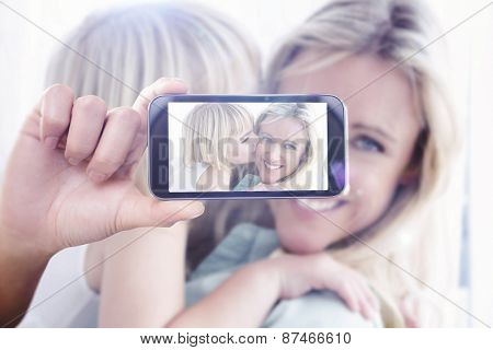 Hand holding smartphone showing against mother sitting on the couch with her daughter kissing her cheek
