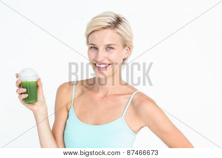 Beautiful woman holding green juice on white background