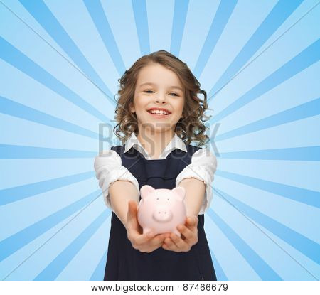 people, money, finances and savings concept - happy girl holding piggy bank on palms over blue burst rays background