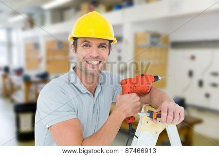 Happy technician holding drill machine while leaning on ladder against workshop