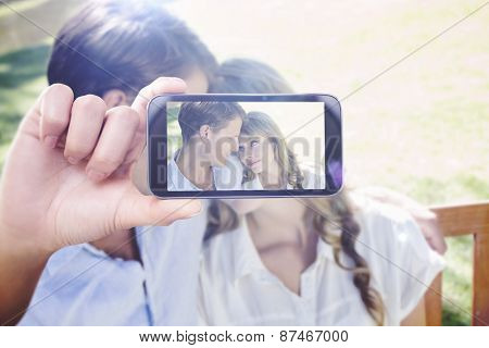 Hand holding smartphone showing against cute couple sitting on park bench together looking at each other
