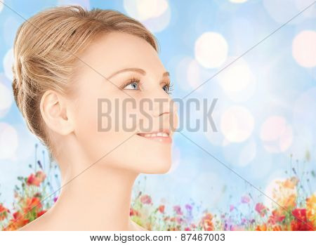 beauty, people and health concept - beautiful young woman face over blue lights and poppy flowers field background