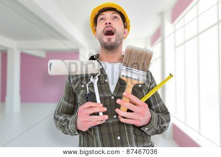 Screaming manual worker holding various tools against modern white and pink room with window