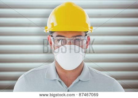 Manual worker against grey shutters
