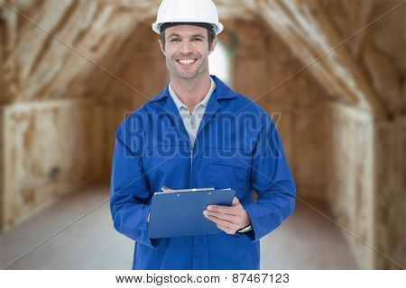 Confident supervisor writing notes against room in house under construction