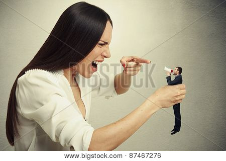 displeased woman holding small man in hand and they shouting at each other. photo on dark background