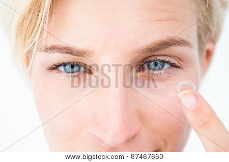 Pretty blonde applying contact lens on white background