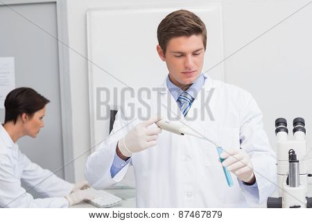 Scientists working attentively with test tube and computer in laboratory