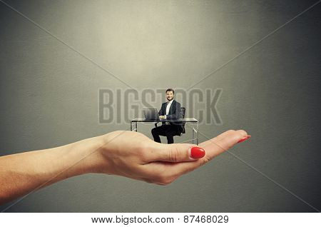 big female palm holding small man at table with computer against dark background