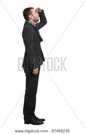 amazed businessman in black suit holding his hand on forehead and looking up into the distance. isolated on white background