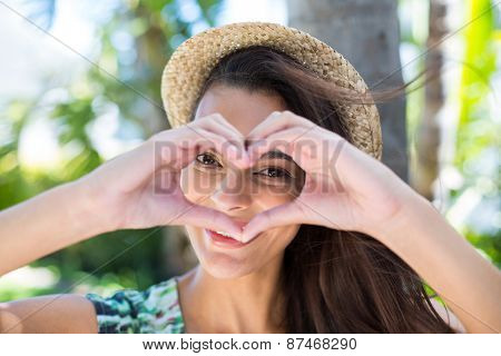 Smiling beautiful brunette doing heart shape with her hands and looking at camera
