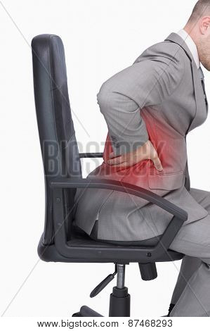 Side view of business man with backache sitting in an office chair over white background