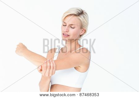Suffering woman touching her sore elbow on white background
