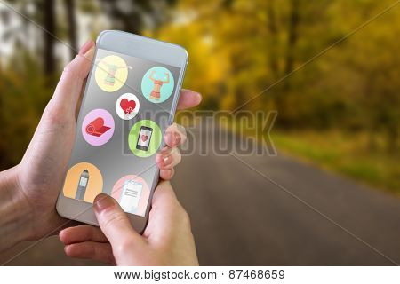 Hand holding smartphone against country road along trees in the lush forest