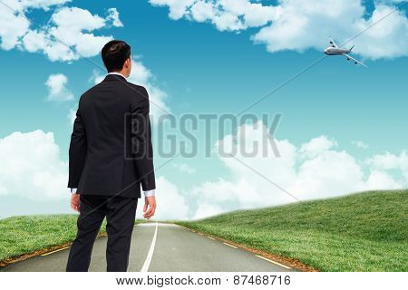 Asian businessman against road leading out to the horizon