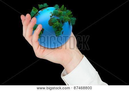 Hand presenting against earth with forest