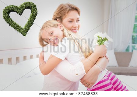 Heart made of leaves against mother and daughter hugging with flowers