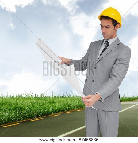 Serious architect with hard hat looking at plans against road leading out to the horizon