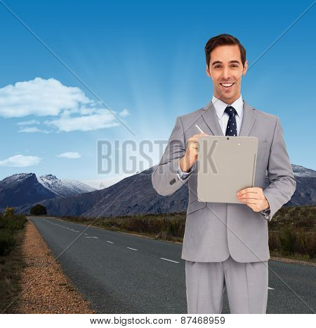 Happy businessman holding a clipboard against road leading out to the horizon