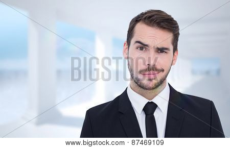 Portrait of a skeptical businessman well dressed against bright white room with columns