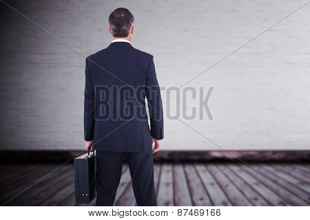 Businessman in suit holding a briefcase against grey room