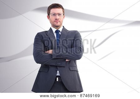 Frowning businessman looking at camera against white wave design
