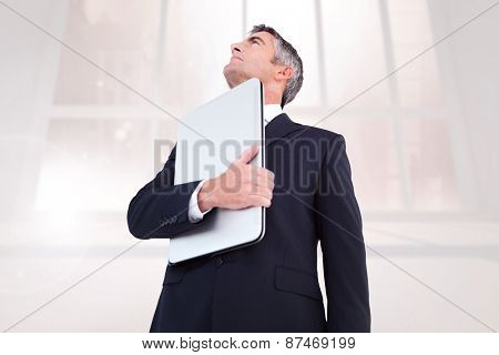 Businessman in suit holding his laptop proudly against bright white room with windows