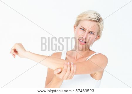 Pretty woman suffering from elbow pain on white background