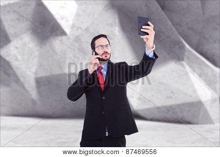 Businessman holding calculator while talking on phone against grey angular background