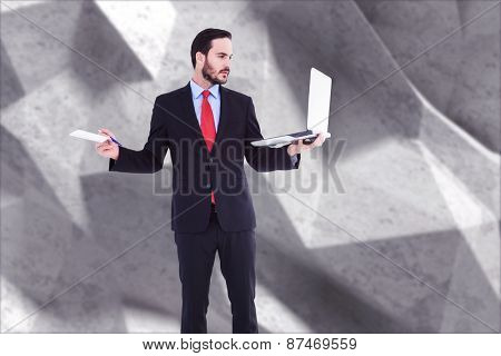 Handsome businessman holding his laptop against grey angular background