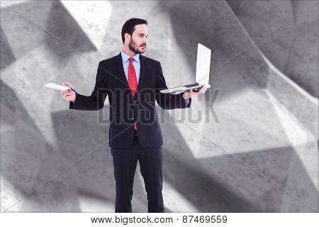 Handsome businessman holding his laptop against grey angular background
