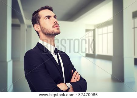 Thinking businessman with his arms crossed against white room with screen