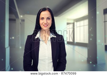 Pretty businesswoman smiling at camera against screen in room with sparks