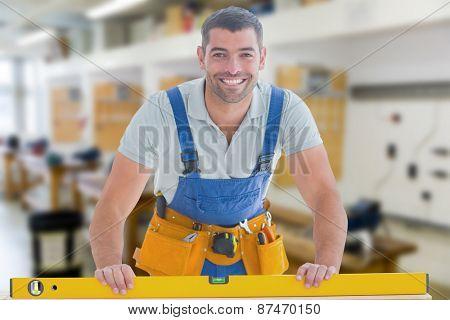 Worker using spirit level against workshop