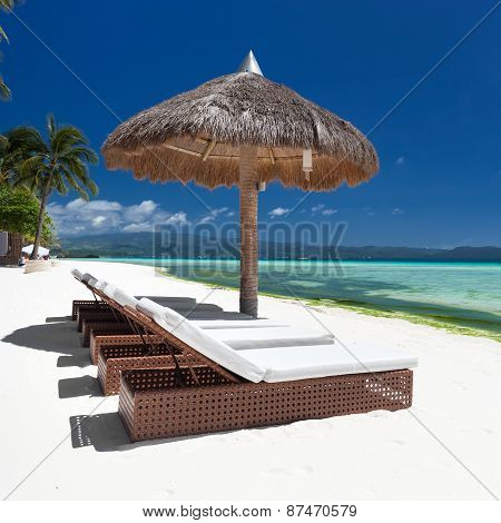 Sun Umbrella And Beach Beds On Tropical Coastline