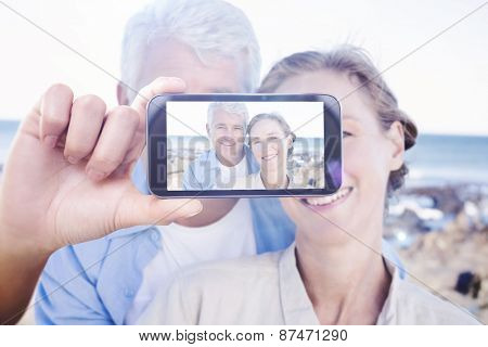 Hand holding smartphone showing against happy casual couple by the coast