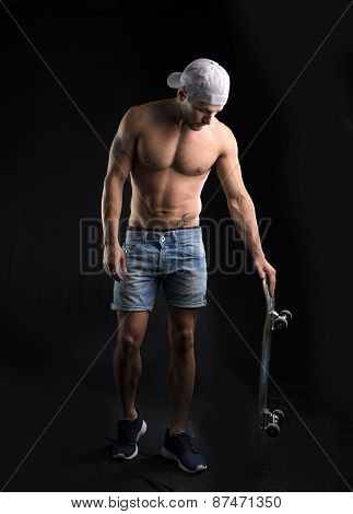 Muscular shirtless young man standing with skateboard