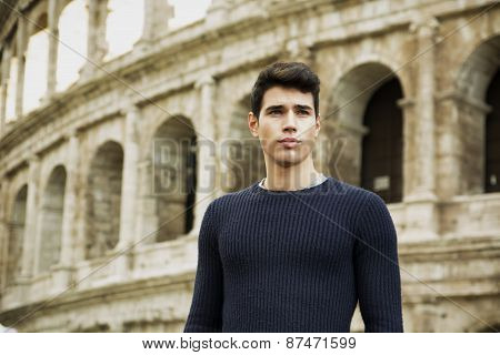 Attractive young man in Rome standing in front of the Colosseum