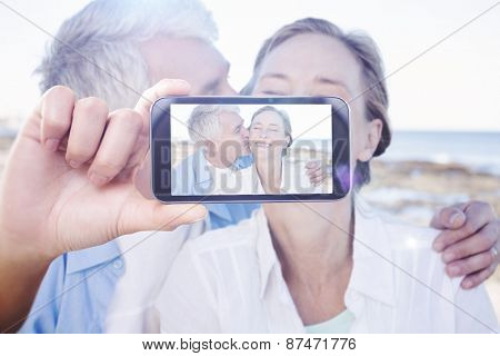Hand holding smartphone showing against casual couple having fun by the sea