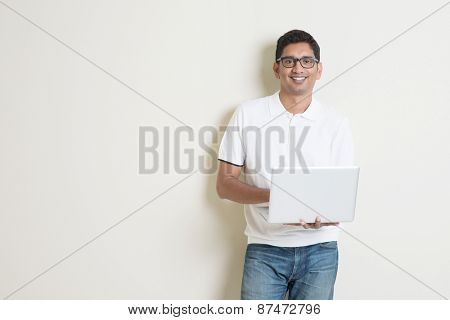 Portrait of handsome Indian guy using laptop computer, standing on plain background with shadow, copy space at side.